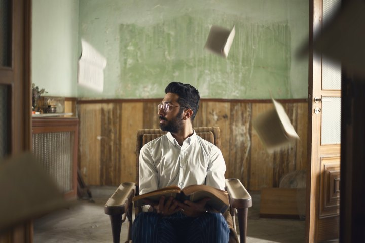A man sits in a chair in the midle of a room while holding a book. There are other books and papers that have been tossed in the air, falling or flying around his head.