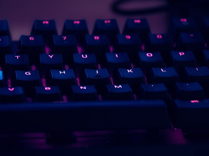 A close-up photograph of a computer keyboard that is backlit. The backlight's glow is purple.