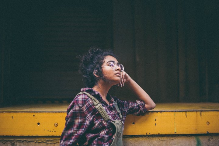 A young woman of color wearing glasses and a flannel shirt leans against a cement structure while looking wistfully to the right.