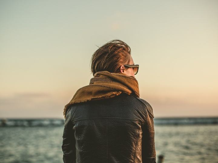A person wearing a leather jacket, a scarf, and sunglasses is looking out over the ocean on a cloudy day.
