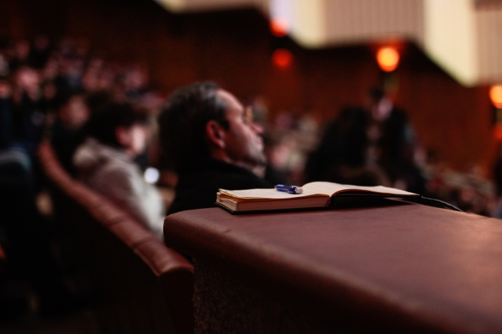 An audience sitting in some kind of theather are in the background. An open book with a pen sitting on top of it is in the foreground.